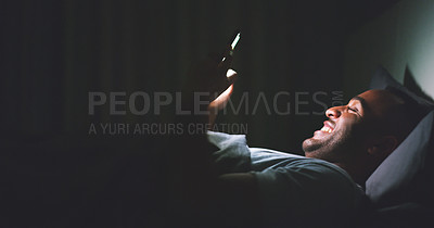Buy stock photo Shot of a cheerful young man using his cellphone while lying in bed late at night