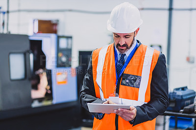 Buy stock photo Cropped shot of a focused male engineer wearing safety gear while doing an inspection on machinery inside of a workshop
