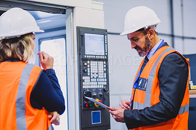 Buy stock photo Cropped shot of two confident engineers doing inspection on machinery together inside of a workshop