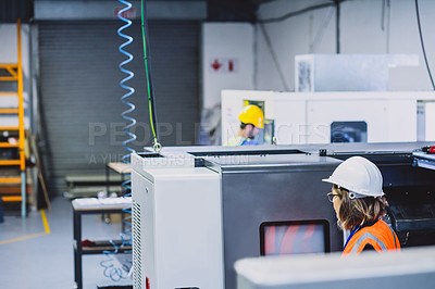 Buy stock photo Cropped shot of a focused female engineer working on her laptop while being seated inside of a workshop