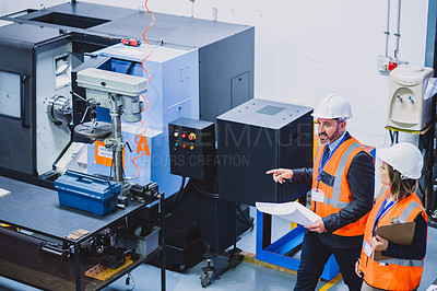 Buy stock photo Cropped shot two confident engineers walking around and doing inspection on machinery inside of a workshop