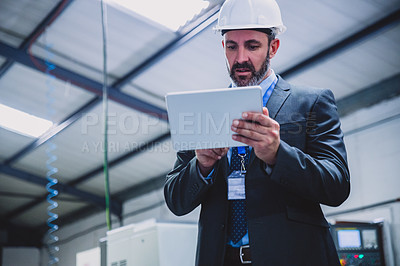 Buy stock photo Cropped shot of a focused male engineer doing inspection while holding a digital tablet inside of a workshop