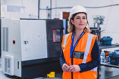 Buy stock photo Cropped shot of a cheerful female engineer standing inside of a workshop during the day