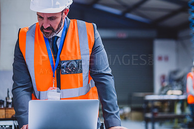 Buy stock photo Cropped shot of a focused male engineer working on a laptop inside of a workshop during the day