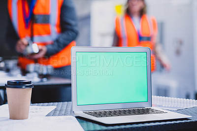 Buy stock photo Cropped shot of a laptop on top of a table with focused engineers working in the background