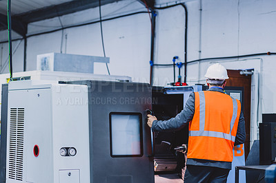 Buy stock photo Rearview shot of an unrecognizable engineer working on a machine inside of a workshop