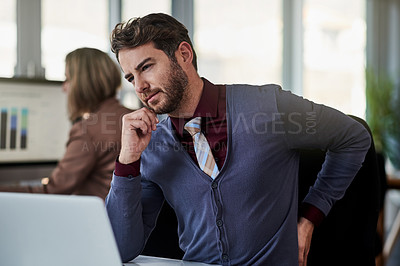 Buy stock photo Shot of a young businessman suffering with back pain while working in an office