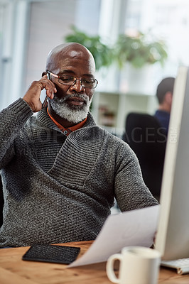 Buy stock photo Shot of a mature businessman talking on a cellphone while going through paperwork in an office