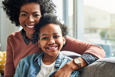 Buy stock photo Cropped shot of a young woman and her daughter sitting together at home