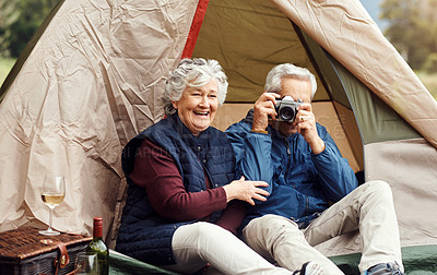 Buy stock photo Shot of a senior man taking photos while camping with his wife in the wilderness