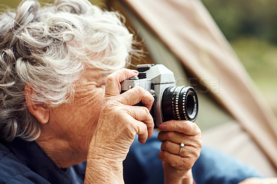 Buy stock photo Shot of a senior woman taking photos while camping in the wilderness