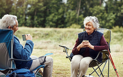 Buy stock photo Shot of a senior woman drinking coffee while camping with her husband in the wilderness