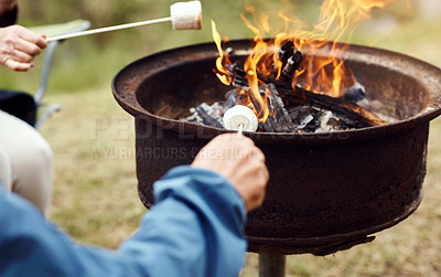 Buy stock photo Closeup shot of a senior couple roasting marshmallows while camping in the wilderness
