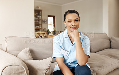 Buy stock photo Cropped portrait of an attractive young nurse sitting alone with her hand on her chin in a nursing home