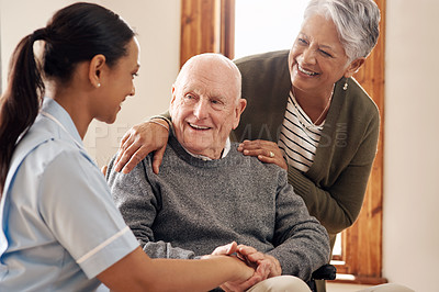 Buy stock photo Cropped shot of an attractive young female nurse standing next to an elderly male tenant in a wheelchair and his wife at an old age home
