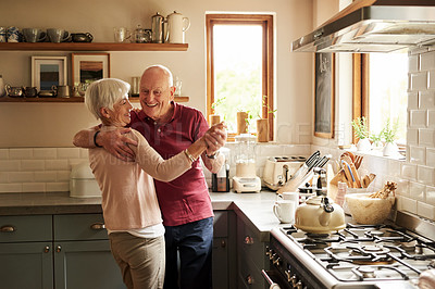 Buy stock photo Cropped shot of a senior couple dancing in the kitchen at home