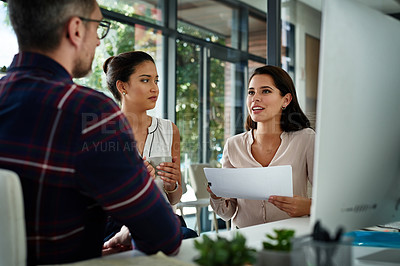 Buy stock photo Cropped shot of a diverse group of businesspeople sitting in the office and using paperwork during a meeting
