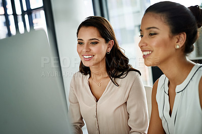 Buy stock photo Cropped shot of two attractive young female colleagues sitting in the office together and working on computers