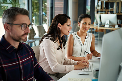 Buy stock photo Cropped shot of a diverse group of businesspeople sitting in the office together and working on computers