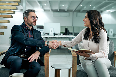 Buy stock photo Cropped shot of an attractive young businesswoman sitting and shaking hands with her male coworker in the office