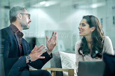 Buy stock photo Cropped shot of two business colleagues sitting in the office together and having a meeting