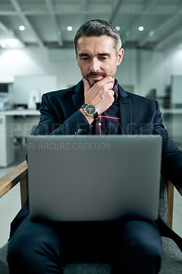 Buy stock photo Cropped shot of a handsome mature businessman sitting alone in his office and looking contemplative while working on his laptop