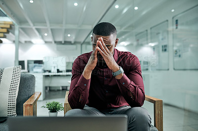Buy stock photo Cropped shot of a handsome young businessman sitting in his office and suffering from a headache while using his laptop