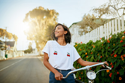 Buy stock photo Cropped shot of an attractive young woman walking and pushing her bicycle during an enjoyable day outside alone