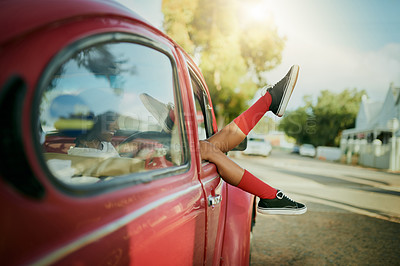 Buy stock photo Cropped shot of an attractive young woman sitting in her car alone with her legs hanging outside the window