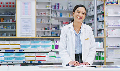 Buy stock photo Portrait of a young pharmacist writing notes while working in a chemist