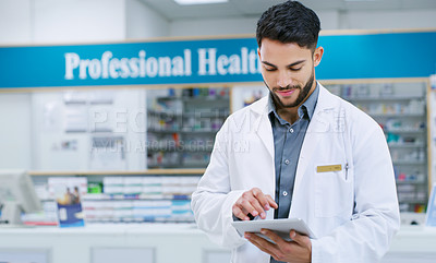 Buy stock photo Shot of a young pharmacist using a digital tablet while working in a chemist