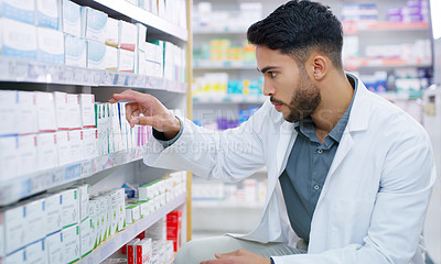 Buy stock photo Shot of a young pharmacist sorting medication on a shelf in a chemist