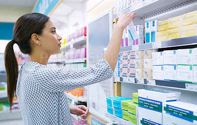 Buy stock photo Shot of a young woman looking at products in a pharmacy