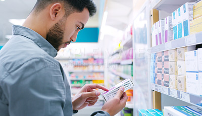 Buy stock photo Shot of a young man looking at products in a pharmacy