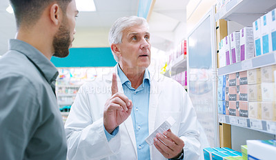 Buy stock photo Shot of a mature pharmacist assisting a customer in a chemist