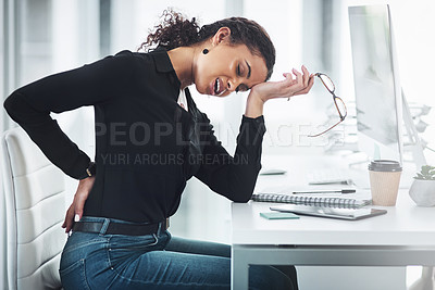 Buy stock photo Shot of a young businesswoman suffering with back ache in an office