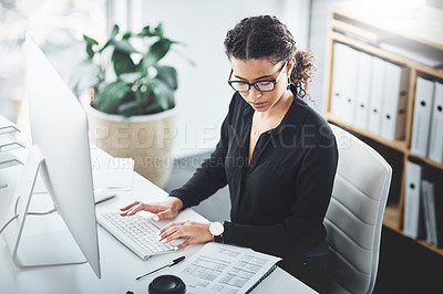 Buy stock photo Shot of a young businesswoman going through paperwork while working on a computer in an office