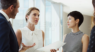 Buy stock photo Cropped shot of a diverse group of businesspeople standing in the office together and reading paperwork during a discussion