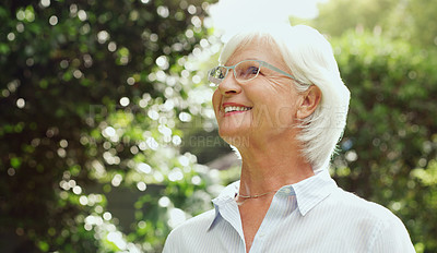 Buy stock photo Shot of a happy senior woman enjoying herself while spending the day outdoors