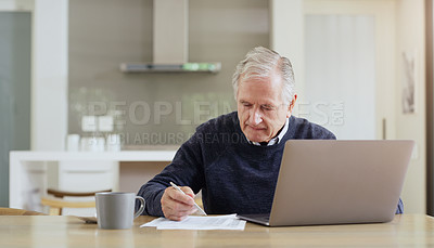 Buy stock photo Shot of a senior man using a laptop while going over his bills and finances at home