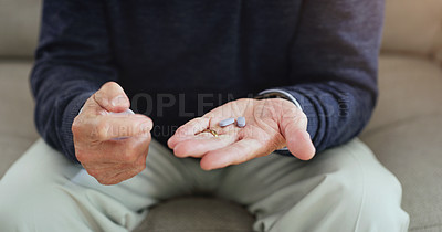 Buy stock photo Shot of an unrecognizable senior man taking his medication at home