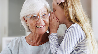 Buy stock photo Shot of an adorable little girl whispering something to her grandmother at home
