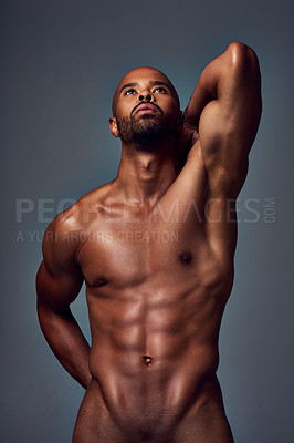 Buy stock photo Studio shot of a muscular young man looking up thoughtfully while posing nude against a grey background
