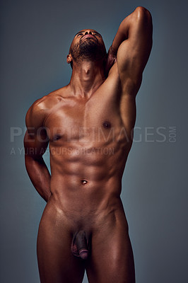Buy stock photo Studio shot of a muscular young man looking up while posing nude against a grey background
