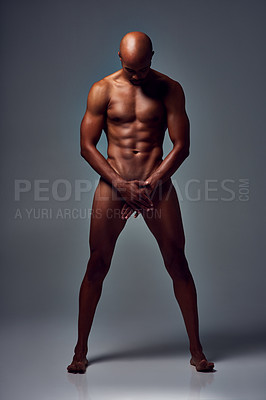 Buy stock photo Studio shot of a muscular young man posing nude with his hands covering his manhood against a grey background