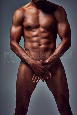 Buy stock photo Studio shot of an unrecognizable muscular young man posing nude with his hands covering his manhood against a grey background