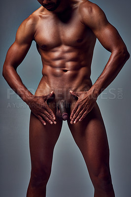 Buy stock photo Studio shot of an unrecognizable muscular young man posing nude with his hands framing his manhood against a grey background
