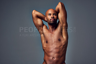 Buy stock photo Studio shot of a muscular young man looking thoughtful while posing nude with his hands behind his head against a grey background