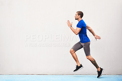 Buy stock photo Full length shot of a handsome young male athlete running along the track