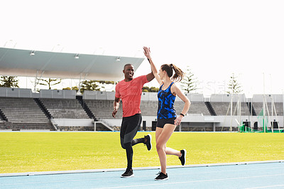 Buy stock photo Full length shot of two young athletes high fiving while running along the track
